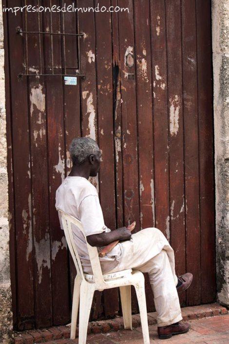 hombre-sentado-y-puerta-Santo-Domingo-impresiones-del-mundo